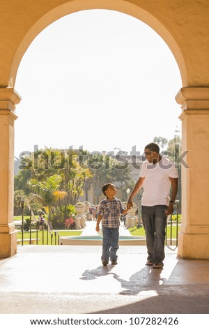 Happy African American Father and Mixed Race Son Holding Hands Walking in the Park. - stock photo