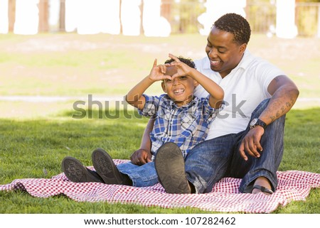 Happy African American Father and Mixed Race Son Making Heart Hand Sign at the Park. - stock photo