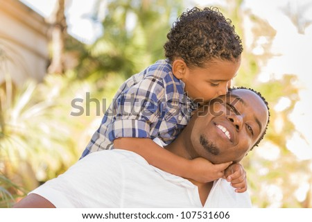 Happy African American Father and Mixed Race Son Playing Piggyback in the Park. - stock photo