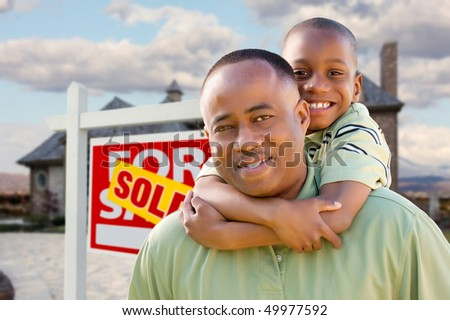 Happy African American Father and Son in Front of New Home and Real Estate Sign. - stock photo