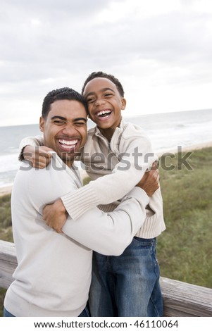 Happy African-American father and ten year old son laughing at beach - stock photo