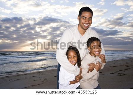 Happy African-American father,  ten year old son and six year old daughter hugging on beach