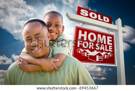 Happy African American Father with Son In Front of Sold Home For Sale Real Estate Sign and Sky.