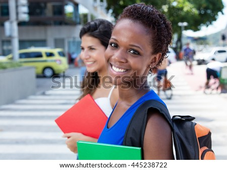 Happy african american female student with caucasian girlfriend - stock photo