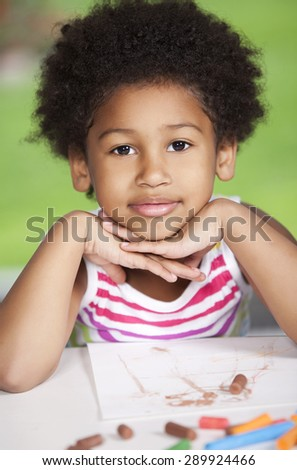 Happy african american girl  drawing with chalk - stock photo
