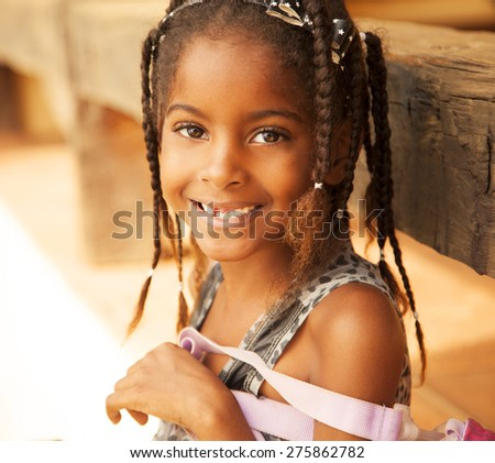 Happy african american girl smiling with backpack, back to school - stock photo