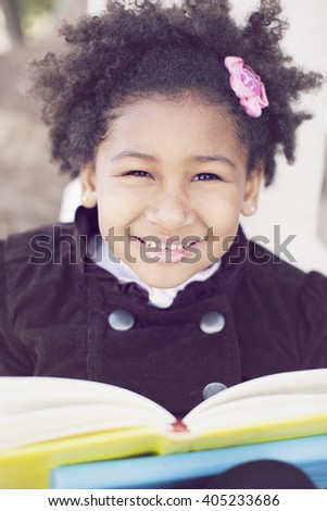 Happy african american little girl reading outdoors - stock photo