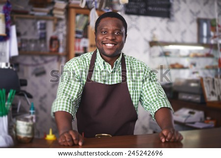 Happy African-american man waiting for clients in cafe - stock photo