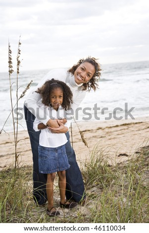 Happy African-American mother and six year old daughter at beach - stock photo