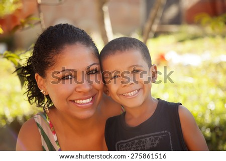 Happy african american mother and son smiling outdoors - stock photo