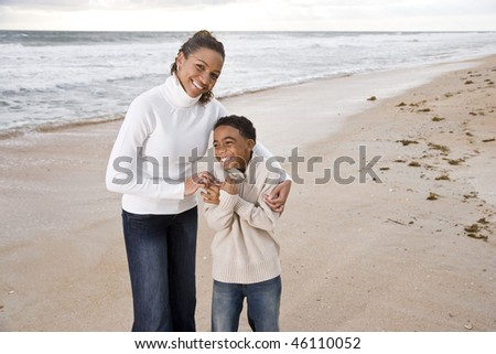 Happy African-American mother and ten year old son standing together on beach - stock photo