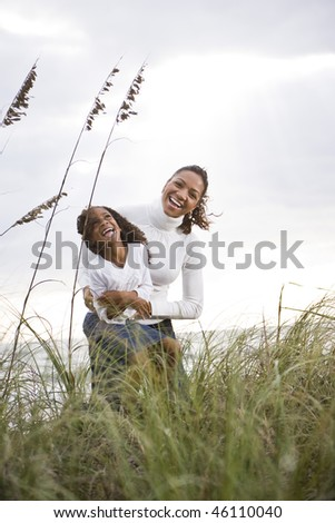 Happy African-American mother hugging and laughing with six year old daughter at beach