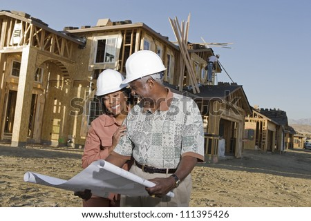 Happy African American senior couple holding blueprint in front of house under construction - stock photo