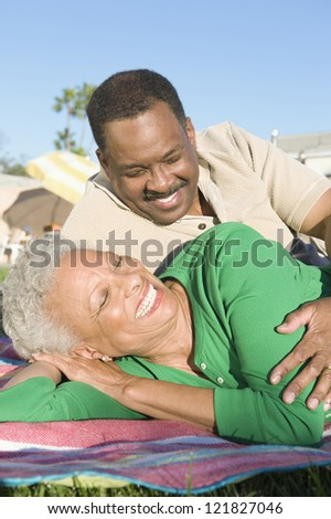 Happy African American senior woman with man relaxing in lawn - stock photo
