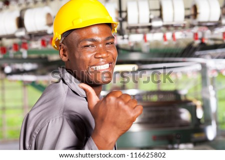 happy african american textile worker thumb up in factory - stock photo