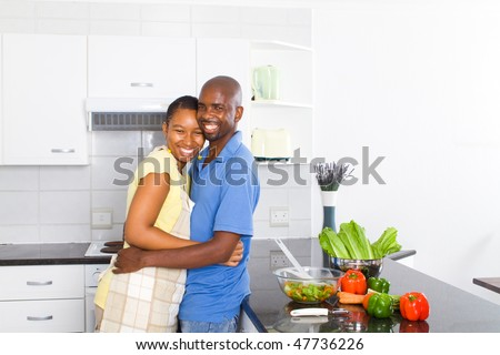 happy african american wife and husband in kitchen