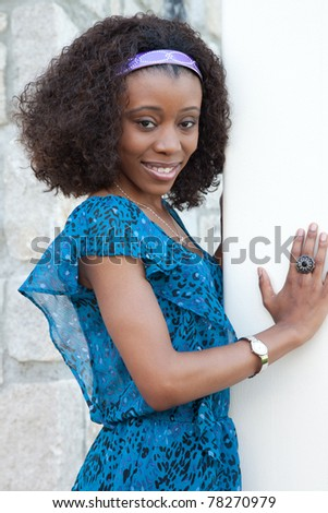 Happy African American woman standing against a wooden pole