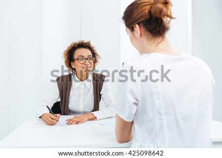 Happy african american young businesswoman in glasses interviewing candidate and writing sitting at the table - stock photo