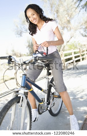 Happy African American young female sitting on cycle with helmet in hand