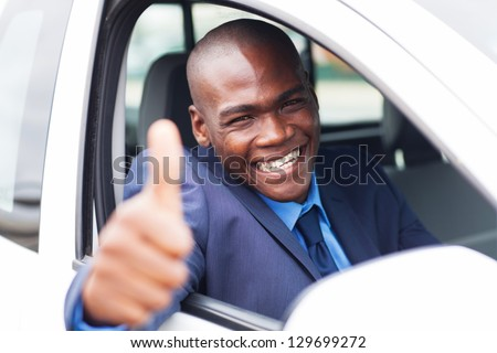 happy african businessman giving thumb up inside new car - stock photo