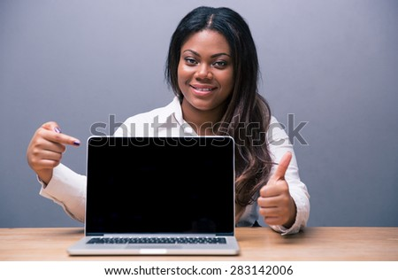 Happy african businesswoman sitting at the table and pointing on blank laptop screen over gray background - stock photo
