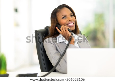 happy african businesswoman talking on the phone - stock photo