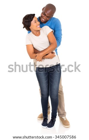 happy african man embracing his beautiful girlfriend from behind - stock photo