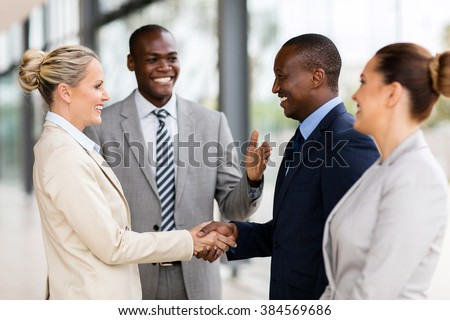 happy african man introducing businesswoman to business partners - stock photo
