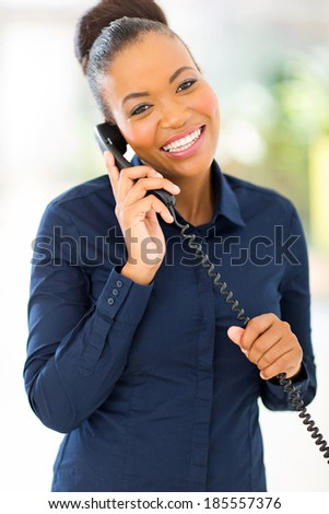 happy african office worker talking on telephone in office - stock photo