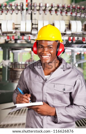 happy african textile factory worker portrait in front of weaving machine - stock photo