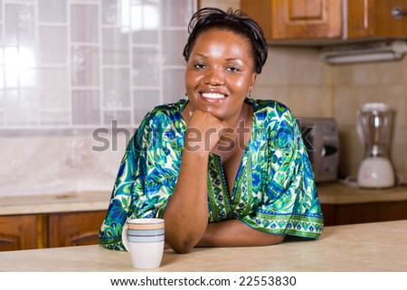 happy african woman drinking coffee in the kitchen - stock photo