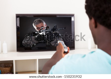 Happy African Young Man Watching Army Solider With Gun In Television At Home - stock photo