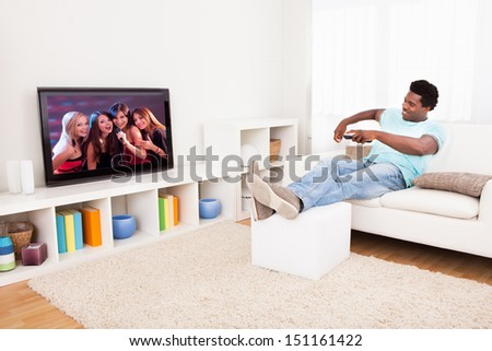 Happy African Young Man Watching Television At Home - stock photo