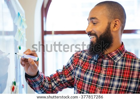 Happy afro american businessman writing something on whiteboard in office - stock photo