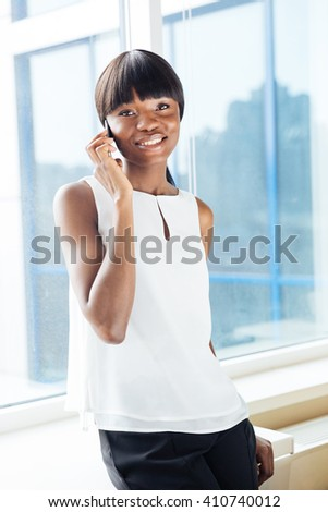 Happy afro american businesswoman talking on the phone in office and looking at camera - stock photo