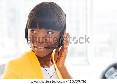 Happy afro american businesswoman working in call center and looking away
