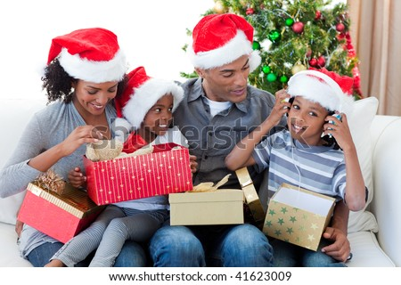 Happy Afro-American family playing with Christmas presents at home - stock photo