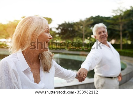 Happy aged couple having great time together in the park - stock photo