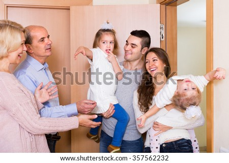 Happy aged couple meeting cheerful kids and grand children at doorstep  - stock photo