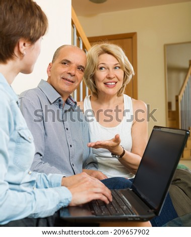 Happy aged couple talking with employee with laptop at home