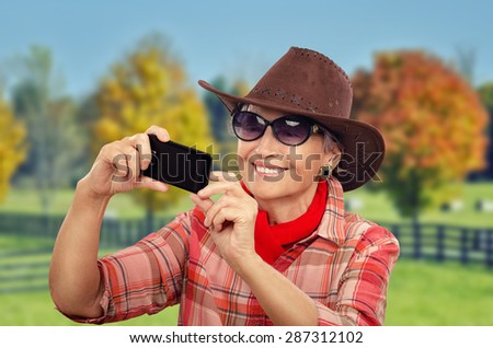 Happy aged cowgirl in red neckerchief is making selfie photo with smart phone. She is wearing brown cowboy hat, red plaid shirt and sunglasses - stock photo