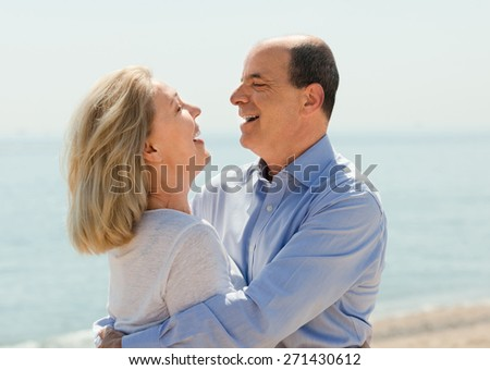 Happy aged lovers laughting outdoor on seaside - stock photo