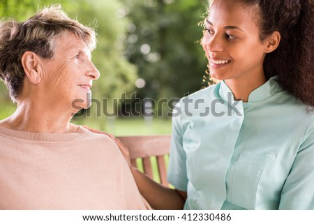 Happy aged woman talking with caring nurse - stock photo