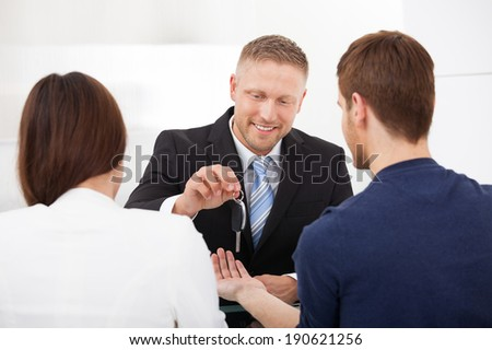 Happy agent giving car key to couple in office - stock photo