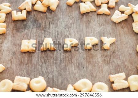 Happy alphabet biscuit on wooden table, stock photo - stock photo