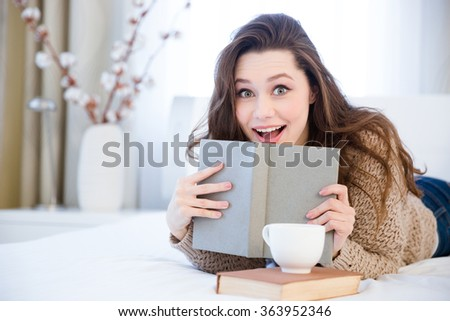 Happy amazed charming young woman lying on bed and reading book in bedroom - stock photo
