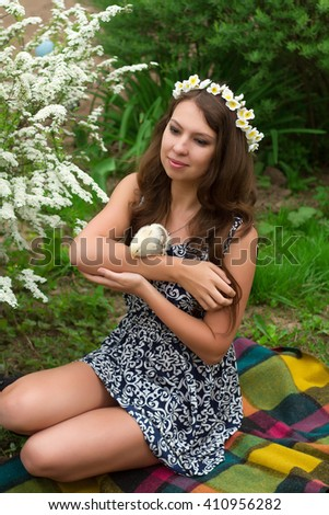 Happy amazing girl with small chickens sitting on her hand outside country house