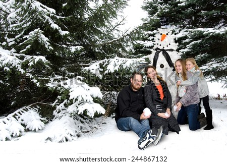 happy American family with snowman Christmas tree in winter woods - stock photo
