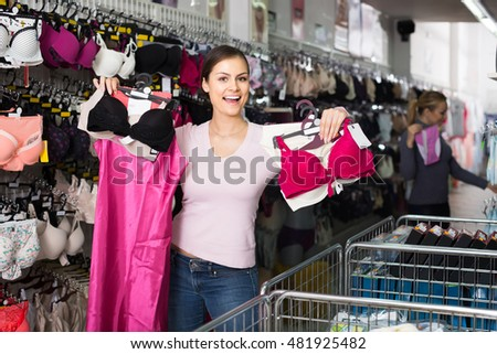 happy american female customer holding various lingerie in hands in underwear store