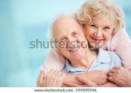 Happy and affectionate elderly couple looking at camera with smiles - stock photo